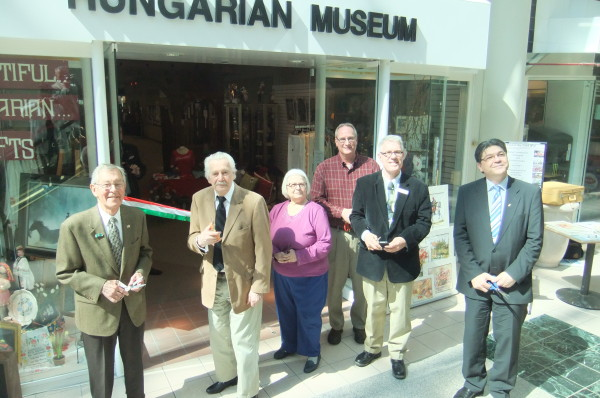 Dignitaries of the ribbon cutting ceremony in front of Museum entrance